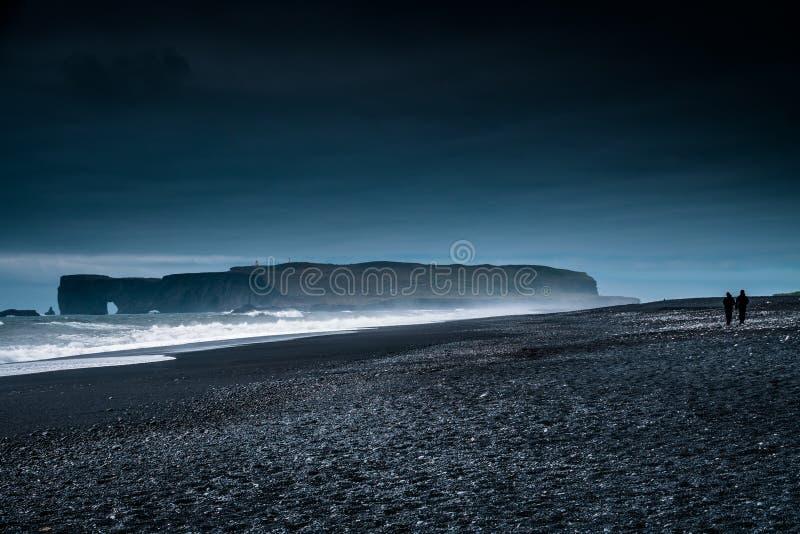 Schwarzer Sand-Strand, dunkle Nacht Islands während des Sonnenaufgangs mit dem Paargehen lizenzfreie stockbilder
