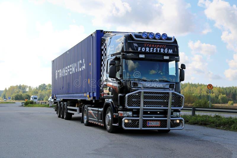 Schwarzer Scania-LKW schleppt einen Behälter lizenzfreies stockbild