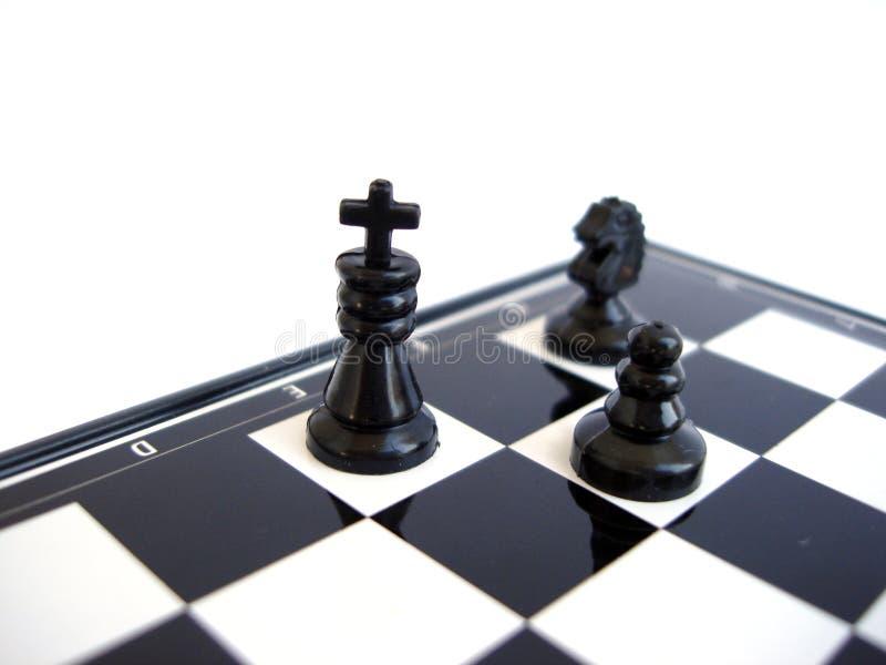 Schwarzer Schachkönig steht mit Abbildung auf einem Schachvorstand stockfotografie