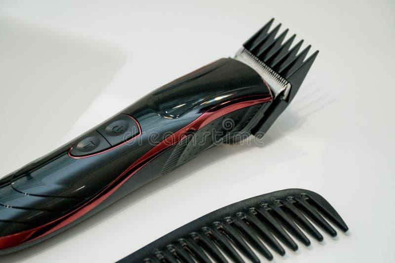 Schwarzer Scherer in einem Badezimmer Junges asiatisches M?dchen, das Haar mit dem Finger getrennt auf wei?em Hintergrund k?mmt stockbilder