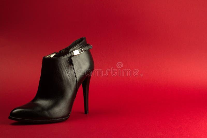 Schwarzer Schuh des hohen Absatzes auf rotem Hintergrund stockfotografie