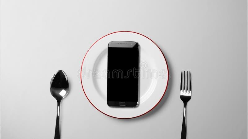 Schwarzer Smartphone auf weißer Platte auf weißem Hintergrund stockbild