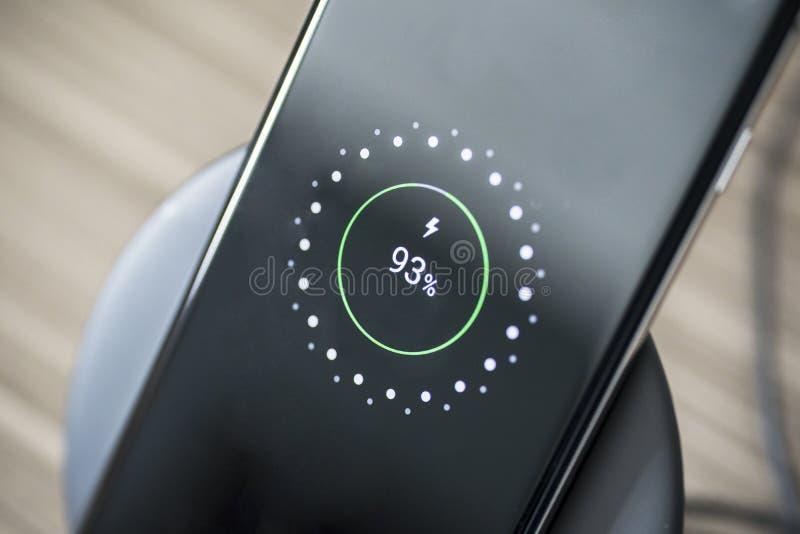 Schwarzer Smartphone, der auf einer Aufladungsauflage auflädt lizenzfreie stockfotos