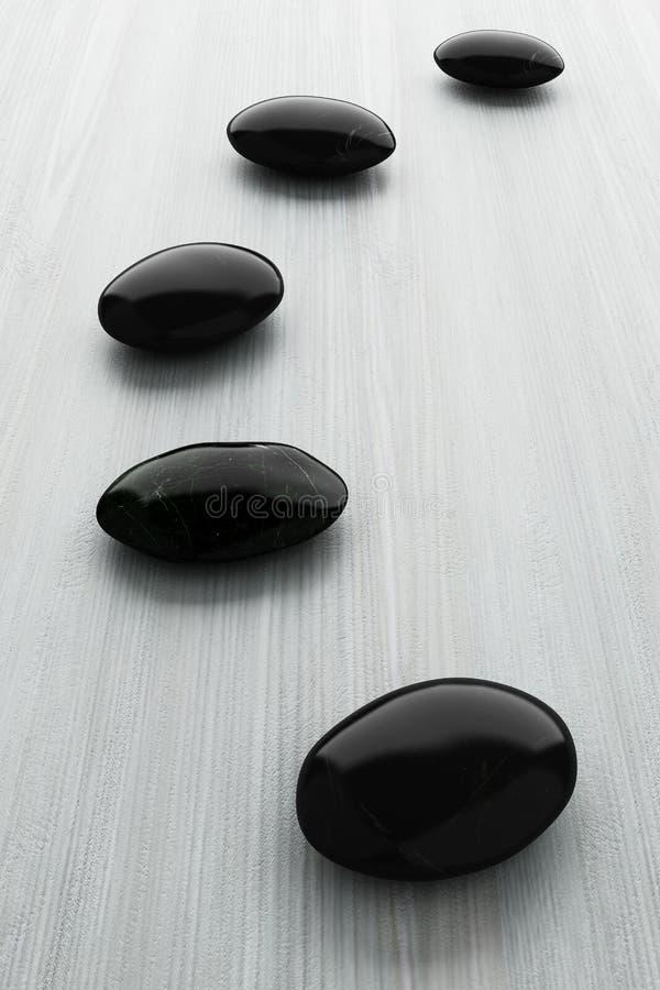 Schwarzer Stein, Zenbadekurort auf weißem Holz stockfoto
