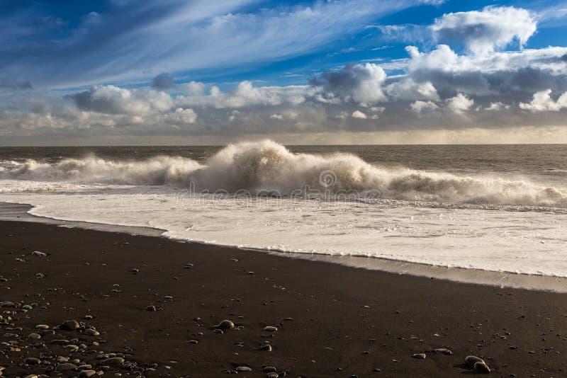 Schwarzer Strand, große Wellen, blauer drastischer Himmel mit Wolken stockfotografie