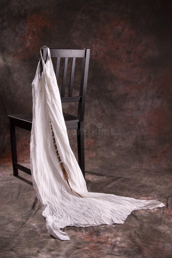 Schwarzer Stuhl mit weißem Kleid lizenzfreie stockbilder