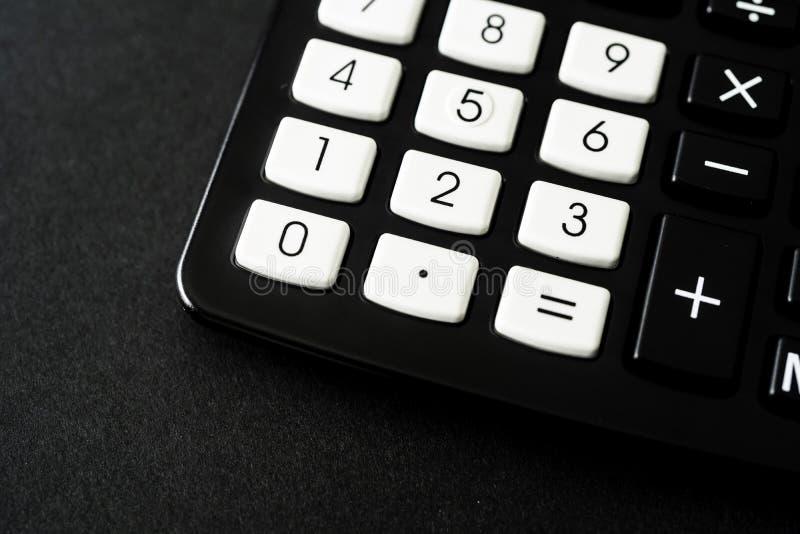 Schwarzer Taschenrechner im Büro auf schwarzem Hintergrund stockfotos