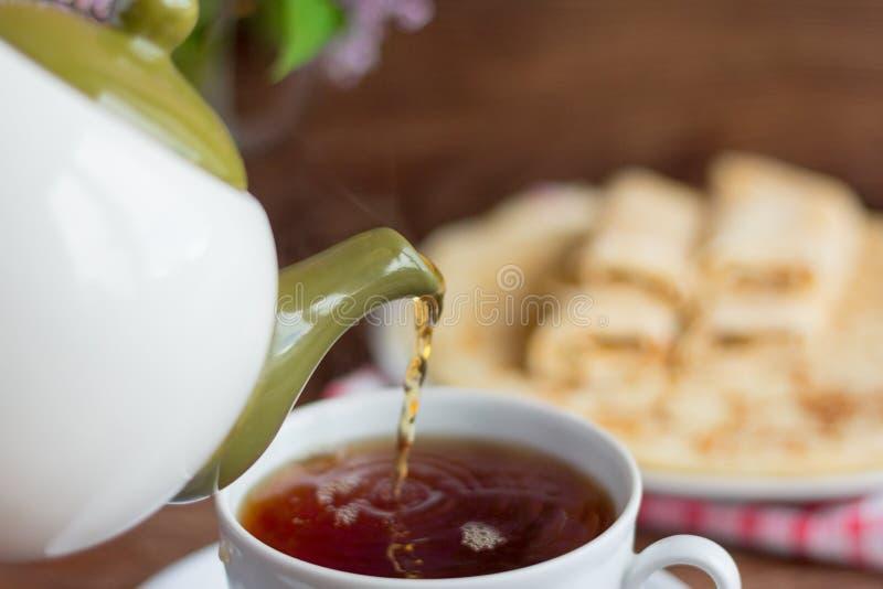 Schwarzer Tee wird in eine Schale zum Frühstück, Nahaufnahme gegossen lizenzfreies stockbild