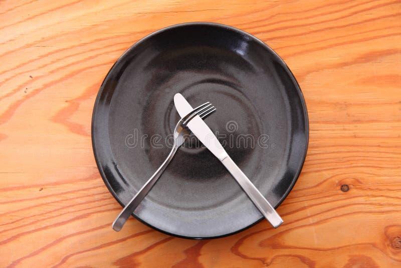 Schwarzer Teller auf dem Holztisch mit Tischbesteckbedeutung MÖGEN NICHT stockfoto