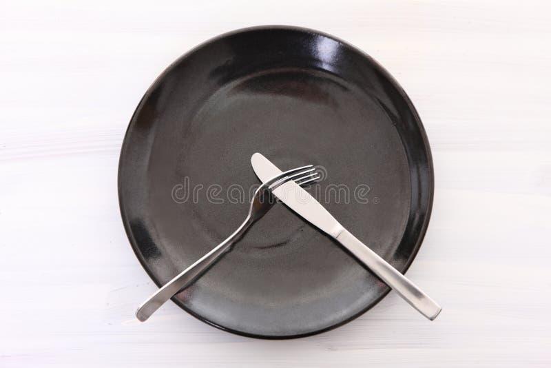 Schwarzer Teller auf dem weißen Holztisch mit Tischbesteckbedeutung MÖGEN NICHT lizenzfreie stockfotos