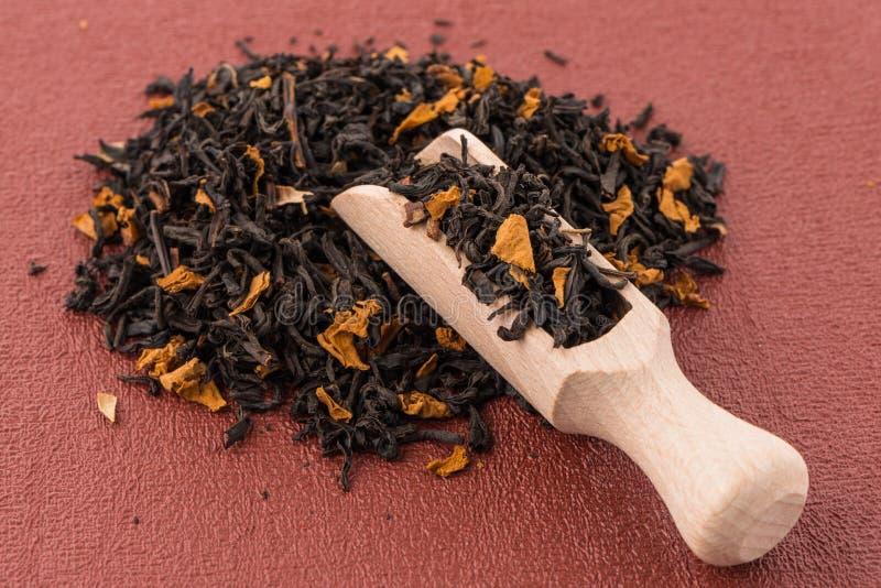 Schwarzer trockener Tee mit einem hölzernen Löffel lizenzfreies stockfoto