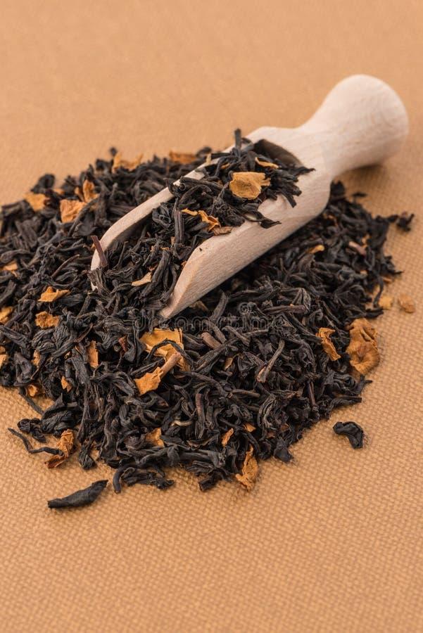 Schwarzer trockener Tee mit einem hölzernen Löffel lizenzfreies stockbild