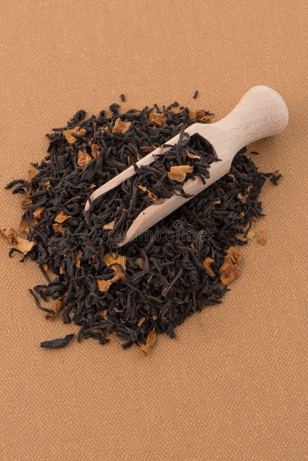 Schwarzer trockener Tee mit einem hölzernen Löffel stockbilder