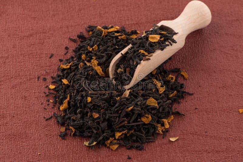 Schwarzer trockener Tee mit einem hölzernen Löffel stockfoto