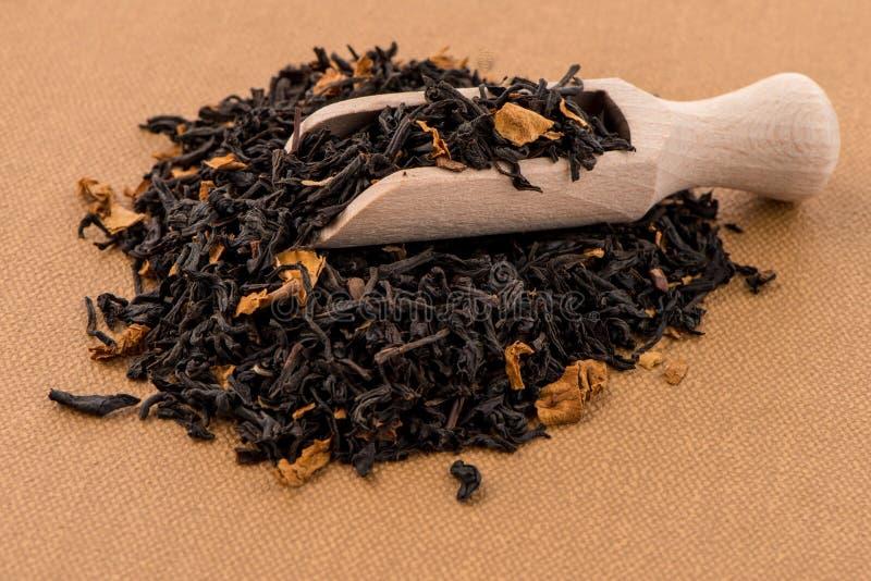Schwarzer trockener Tee mit einem hölzernen Löffel lizenzfreie stockbilder