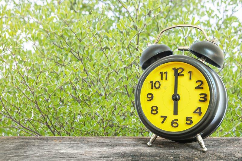 Schwarzer und gelber Wecker der Nahaufnahme für verzieren in 6 O-` Uhr auf altem braunem hölzernem Schreibtisch auf grünen Blätte lizenzfreies stockfoto