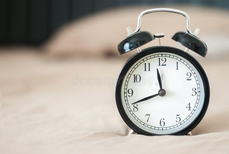 Schwarzer Wecker mit dem Hintergrund weich stockbilder