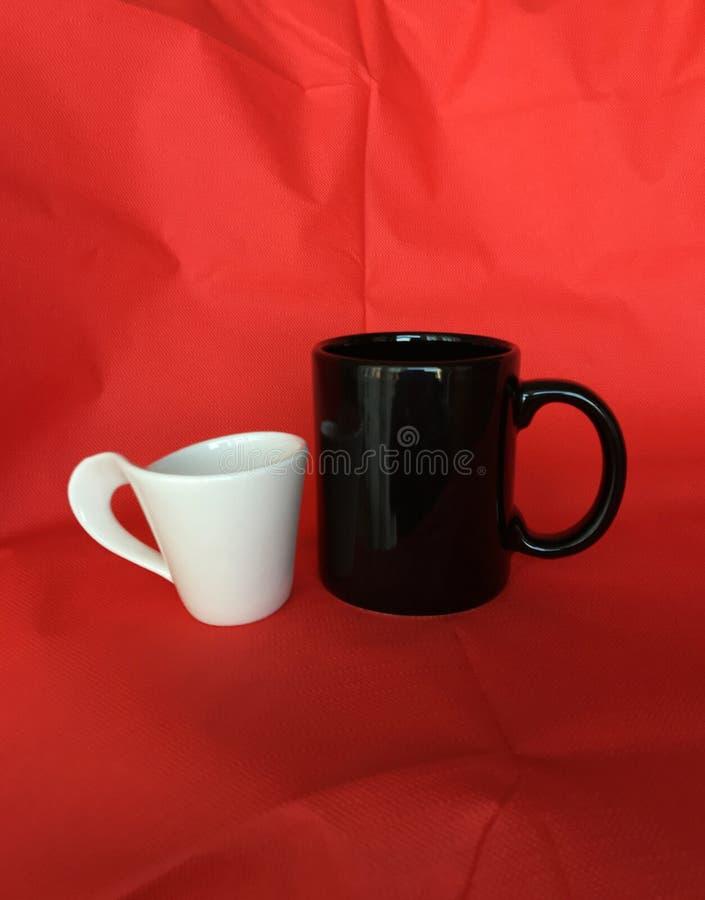 Schwarzer weißer Kaffee oder Teeschalen mit rotem Gewebehintergrund stockbilder