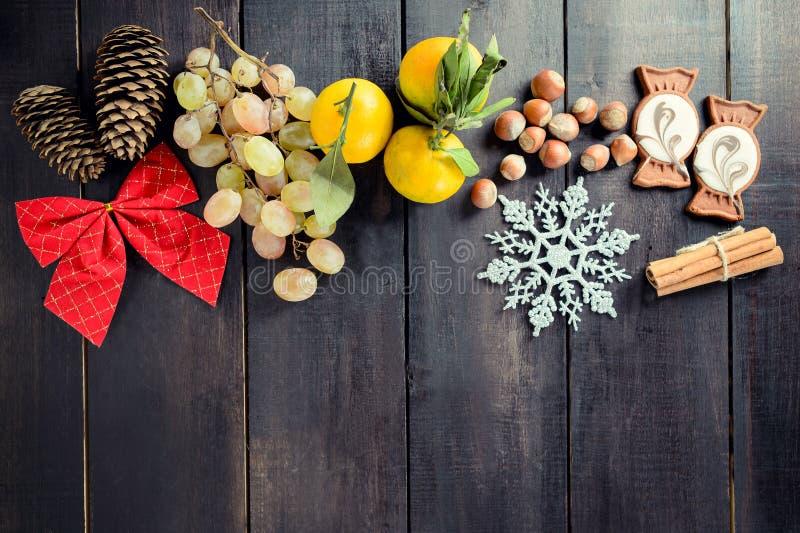 Schwarzer Weihnachtshintergrund mit leerem Kopienraum Trauben, Tangerine und Nüsse lizenzfreie stockbilder