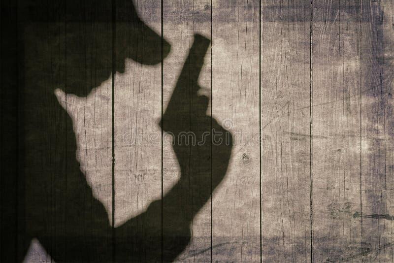 Schwarzes bewaffnetes männliches Schattenbild auf dem Bretterzaun stockfoto
