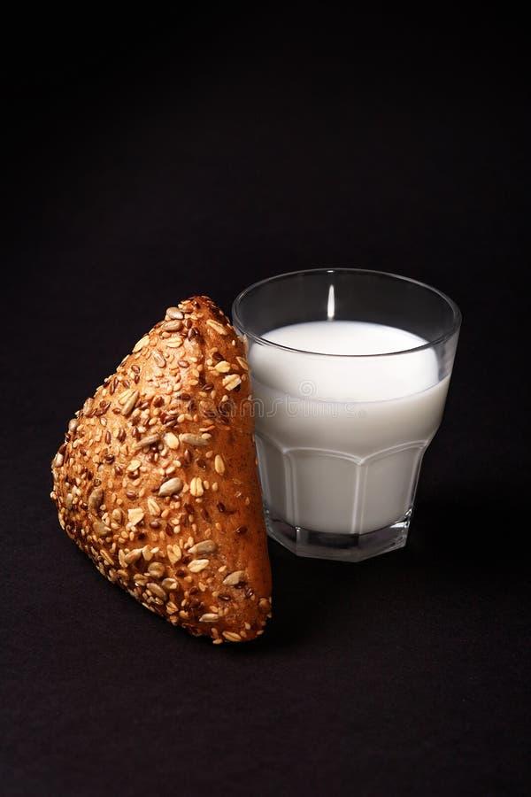 Schwarzes Brötchen mit Samen und Milch Lokalisiert auf Schwarzem lizenzfreies stockbild