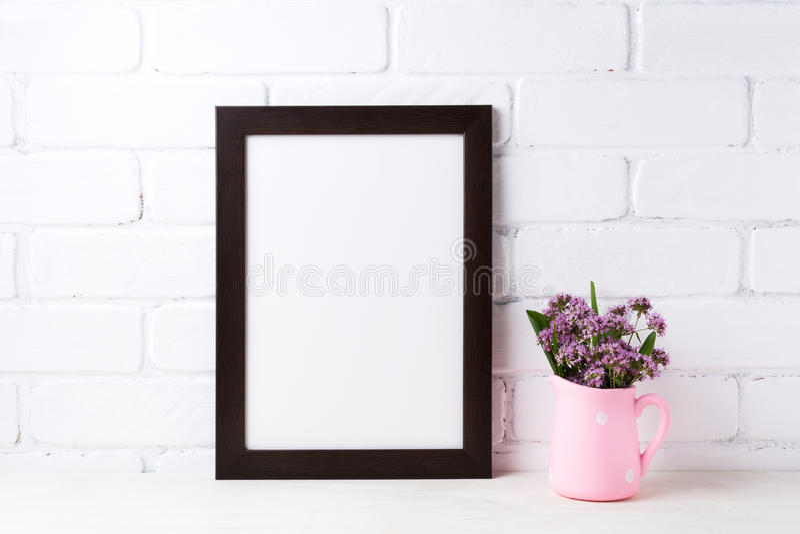 Schwarzes braunes Rahmenmodell mit purpurroten Blumen im Tupfenrosa lizenzfreie stockbilder