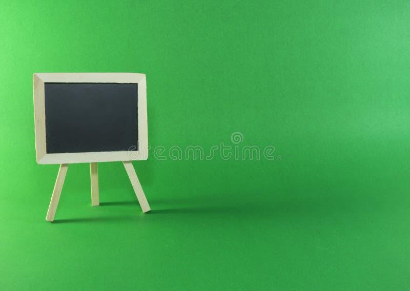 Schwarzes Brett mit Kopienraum auf grünem Hintergrund stockbilder