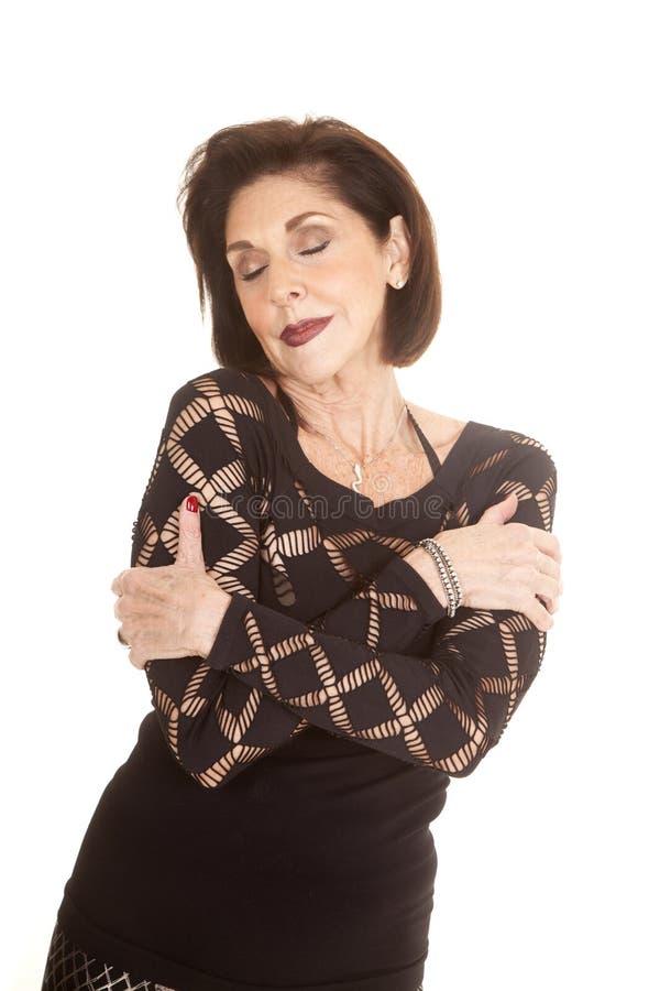 Schwarzes der älteren Frau kleidet die gekreuzten geschlossenen Augen der Arme stockfotos