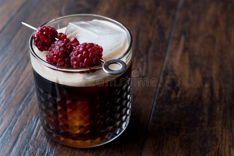 Schwarzes/dunkles Bier-Cocktail mit Brombeeren und Eis auf Holzoberfläche stockbild