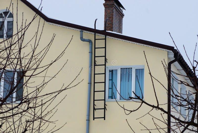 Schwarzes Eisentreppenhaus auf der braunen Fassade eines privaten Gebäudes mit einem Fenster lizenzfreies stockbild