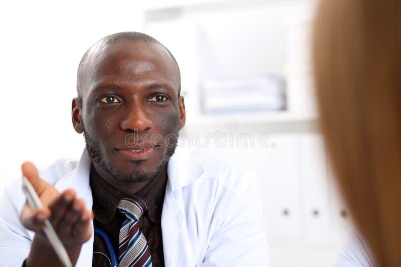 Schwarzes enthäuteter männlicher Doktor verständigen sich mit Patienten stockfotos