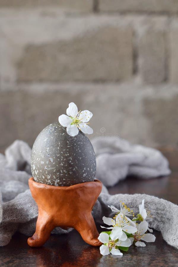 Schwarzes farbiges Ei auf Lehmplatte Glückliche Ostern-Karte Feiertagsfrühstückskonzept Festliche Tabellengedeckdekoration lizenzfreie stockfotografie