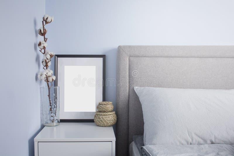 Schwarzes Flammenplakatmodell im gemütlichen skandinavischen Schlafzimmer mit blauen Wänden Skandinavischer Schlafzimmerinnenraum lizenzfreies stockbild