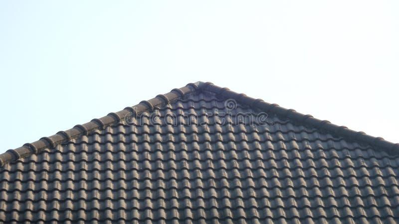 Schwarzes Fliesendach auf einem neuen Haus mit blauem Himmel stockfotografie