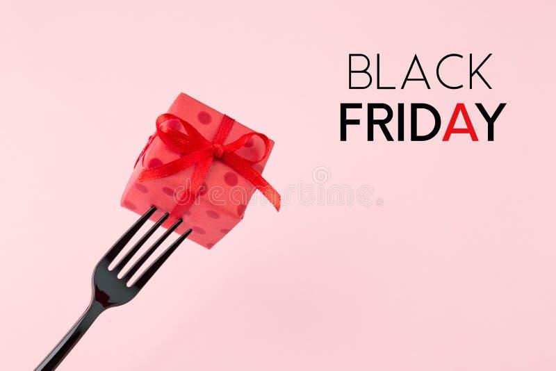Schwarzes Freitag-Konzept mit Geschenkbox und schwarzer Gabel auf rosa backgr lizenzfreie stockfotos