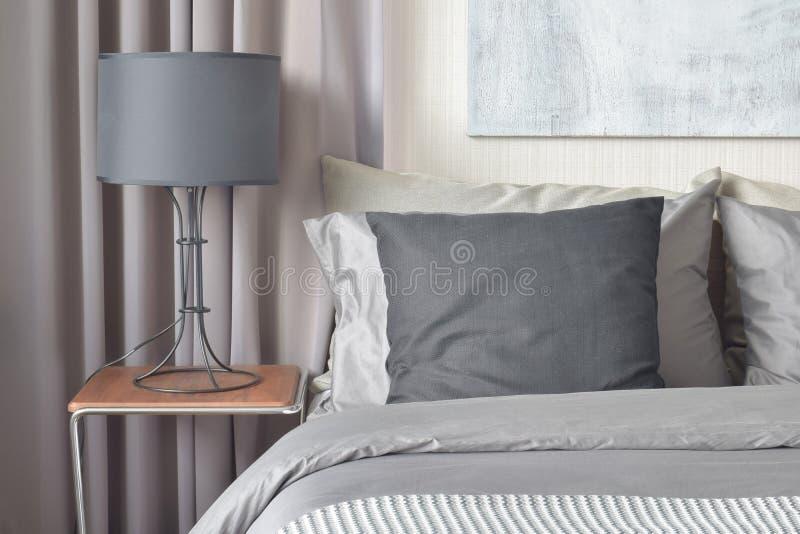 Schwarzes Kissen auf Bett und schwarze Schirmlampe auf Nachttisch stockfotografie
