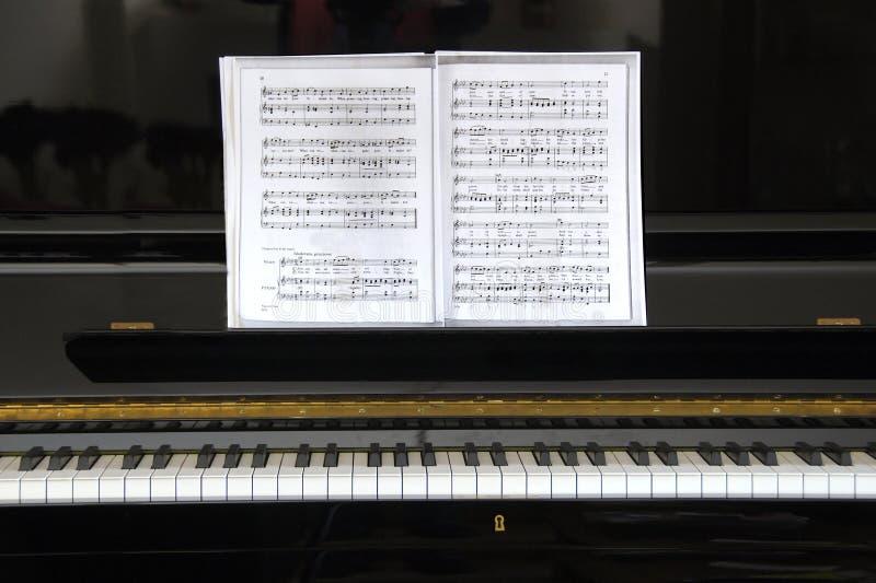 Schwarzes Klavier mit Blattmusik lizenzfreie stockfotos