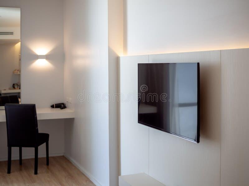 Schwarzes LED-Fernsehen auf weißer Wand nahe Make-upecke mit schwarzem Stuhl im Hotelzimmer lizenzfreie stockbilder