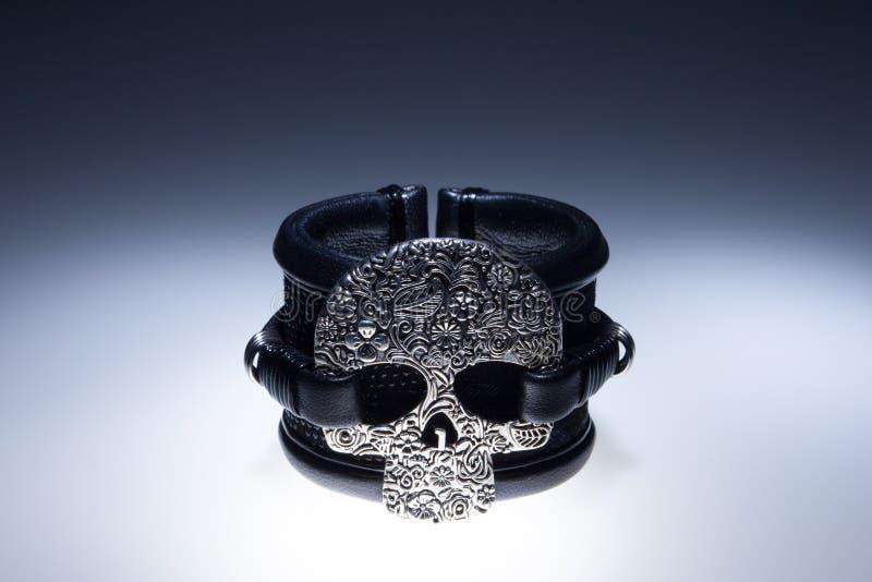 Schwarzes Lederarmband mit Metallschädelanhänger und schwarze Steine stockbild