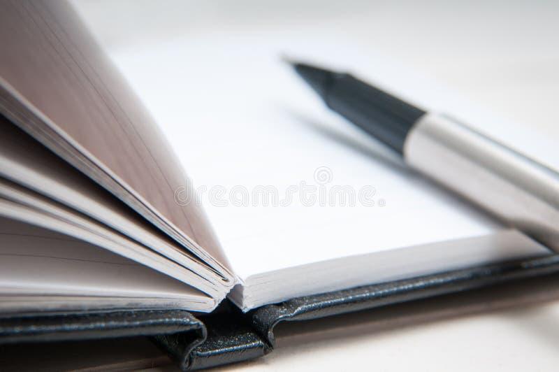 Schwarzes ledernes Notizbuch stockbild