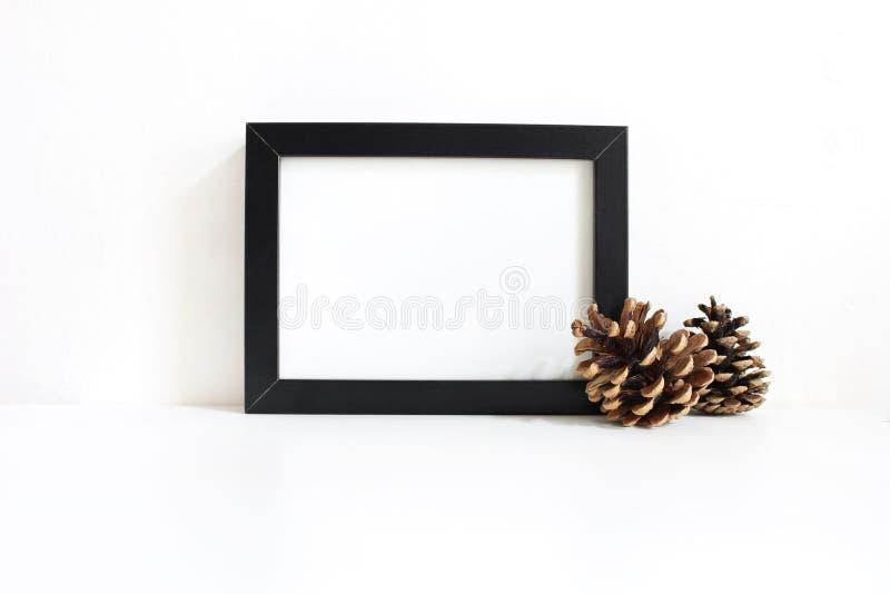 Schwarzes leeres Holzrahmenmodell mit den Kiefernkegeln, die auf der weißen Tabelle liegen PlakatKonzeption des Produkts Angerede lizenzfreie stockfotografie