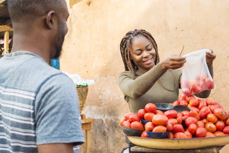 schwarzes Mädchen, das Tomaten auf einem lokalen afrikanischen Markt verkauft, um einen Kunden lächelnd lächelnd stockbild
