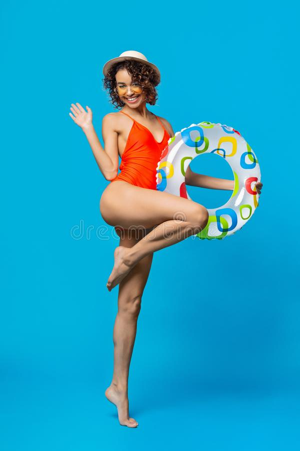 Schwarzes M?dchen im Badeanzug, der geht, mit aufblasbarem Ring auf den Strand zu setzen stockfotografie