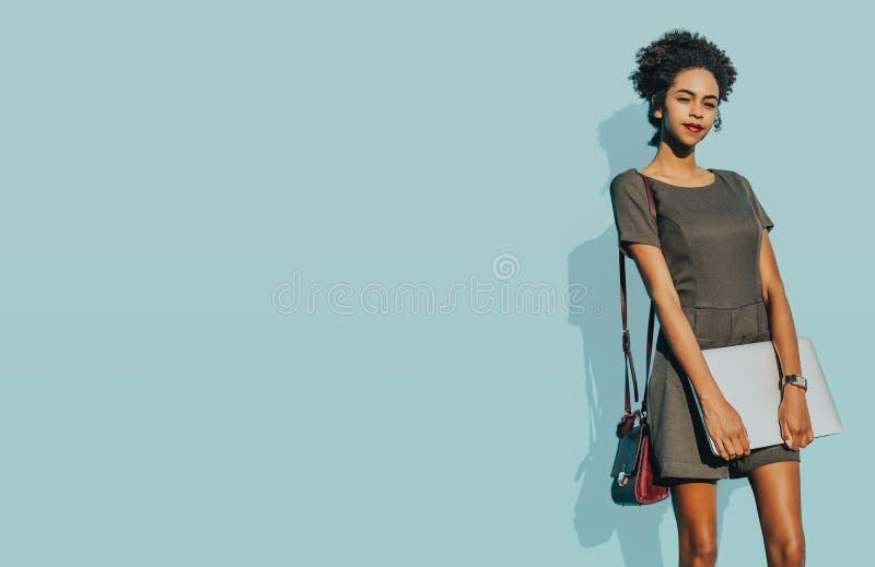 Schwarzes Mädchen mit netbook vor einer Knickentenwand stockfoto