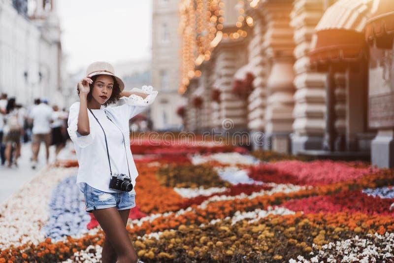 Schwarzes Mädchen mit Retro- Nocken auf der Straße nahe Blumenbeet lizenzfreies stockfoto