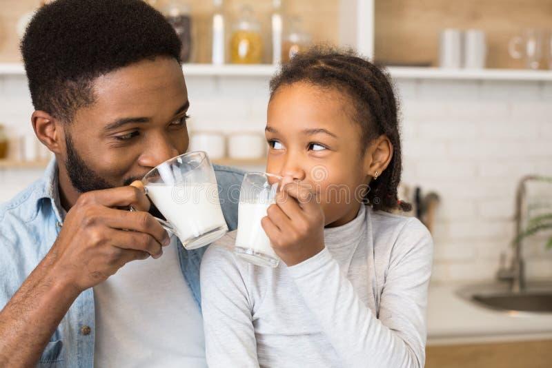 Schwarzes Mädchen und ihr Vater, die frische Milch trinkt lizenzfreies stockbild