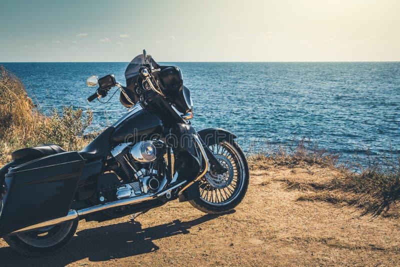 Schwarzes Motorrad auf schöner Seeküste und blauem Himmel vorwärts Grasland, Steppe, Sommer stockfotos