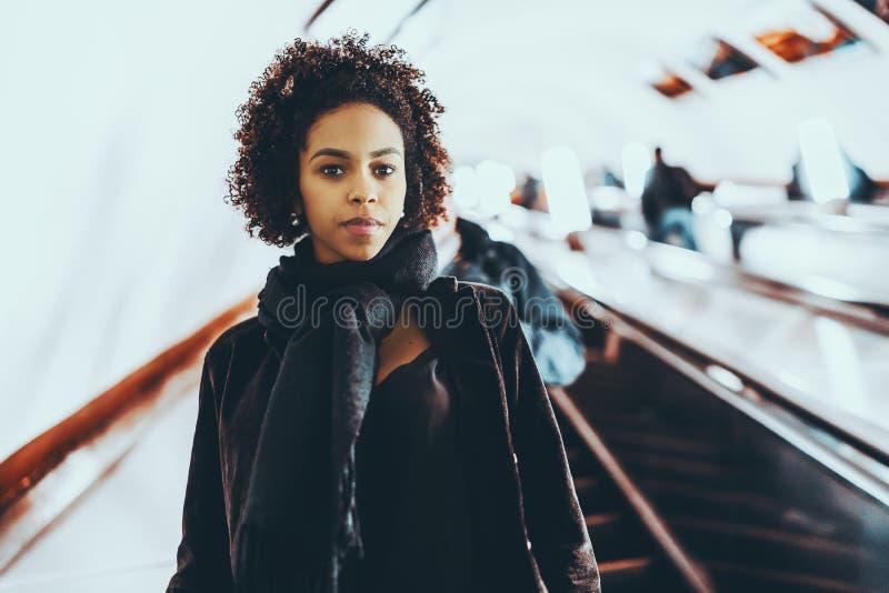 Schwarzes nettes Mädchen, das auf Rolltreppe steht stockbilder