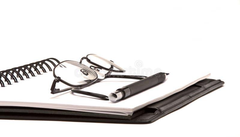Schwarzes Notizbuch mit Feder und Gläsern stockfoto