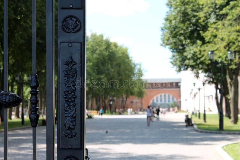 Schwarzes openwork offenes Tor auf dem Hintergrund des Ziegelsteinbogens und -parks stockbild
